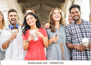 Happy millennials friends having fun together - Young students drinking coffee and laughing together in old town street- Youth lifestyle, school and friendship concept - Main focus on indian man face