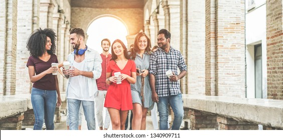 Happy millennials friends having fun together - Young students drinking coffee and laughing together in old town street- Youth lifestyle, school and friendship concept - Main focus on center girl face