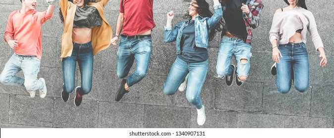 Happy millennials friends jumping outdoor for celebrating - Young people having fun together laughing and smiling - Youth, city lifestyle, team, multiracial, friendship concept - Focus on hands