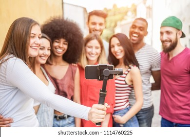 Happy millennials friends making video feed with smartphone outdoor - Young people having fun with new technology trends - Youth lifestyle and social media concept - Focus on phone gimbal