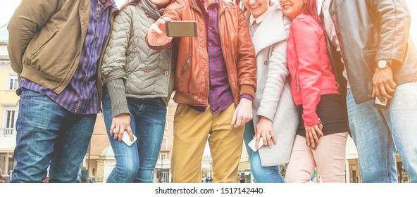 Happy millennials friends making video with smartphone - Young students people having fun with new trends technology - Tech, youth lifestyle and multiracial concept - Focus on center hands