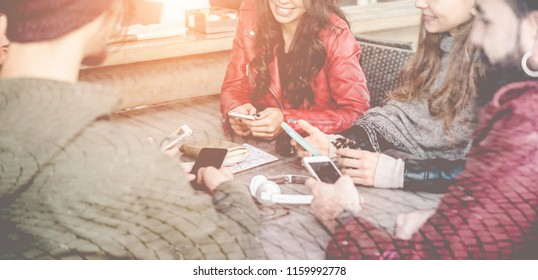 Happy millennials friends using smartphones inside bar - Young trendy people having fun with mobile phones - Generation z, and technology trends concept - Focus on left girl mouth - Window view