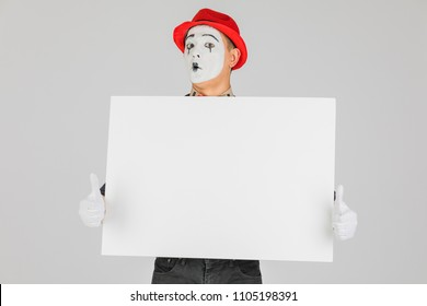 happy MIME artist holding a blank white Board, on a white background