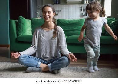 Happy mindful single mother doing morning exercises in yoga pose with kid daughter playing at home, smiling young mom having fun practicing meditation relaxing on stress free weekend with child girl