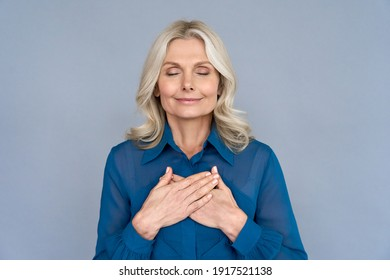 Happy mindful thankful middle aged old woman holding hands on chest meditating with eyes closed isolated on grey background feeling no stress, gratitude, mental health balance, peace of mind concept.