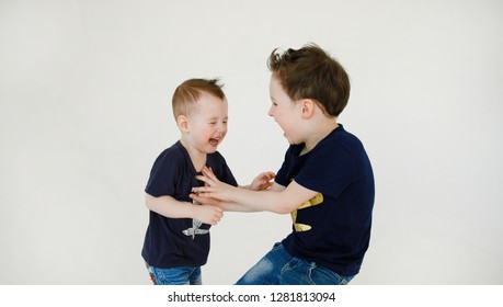 Happy and mischievous brothers during the game. Two rational and active little boys frolic and tickle with each other with a laugh isolated on a white background. Childhood.Positive emotions.Lifestyle