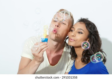 Happy mixed couple. Portrait of a blond young man and his beautiful mulatto girlfriend playing with bubble blower smiling, isolated on white background