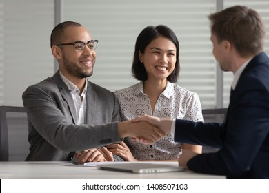 Happy mixed ethnicity young family couple clients customers handshake bank manager agent make agreement mortgage deal taking loan buying insurance investing savings shake hand of male insurer broker