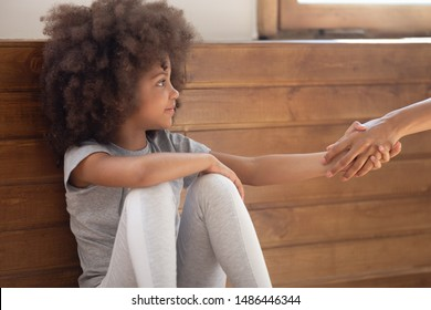 Happy mixed race adorable little girl holding lent hand, accepting psychological help or forgiving offense. Orphan cute child holding hand of foster parent, new adopting family, charity concept.