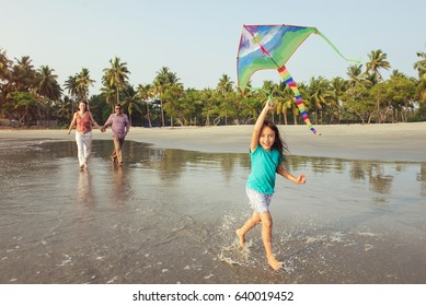 Happy mixed race asian family playing and having fun with child on the sea beach at sunset. Little girl running on the coastline with kite in the hands. Family holiday and togetherness.
