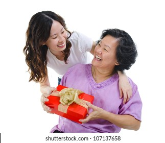 Happy Mixed race Asian mother receiving present from her daughter - Shutterstock ID 107137658
