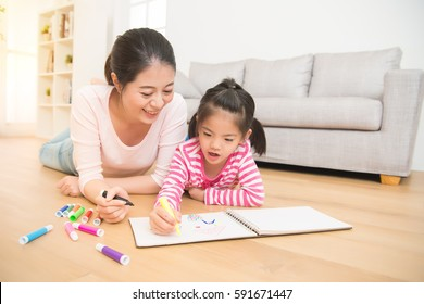 Happy mixed race asian mother and daughter together paint. adult woman helps the child girl lying down on wooden floor drawing sketchbook in the living room at home. family activity concept.
