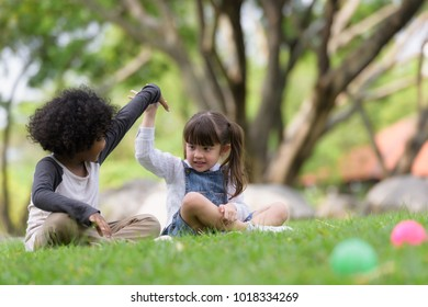 Happy Mixed race boy and girl  playing colorful balls and having fun in park .kid, child, school ,children,education preschool concept .