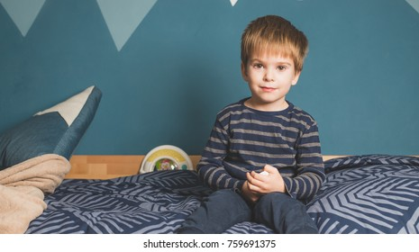 happy mixed race boy sitting on bed