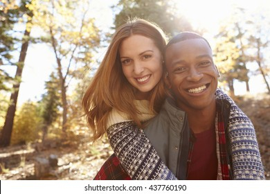 Happy mixed race couple embracing during hike in a forest