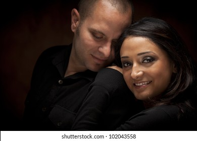 Happy Mixed Race Couple Flirting with Each Other Portrait Against A Black Background.