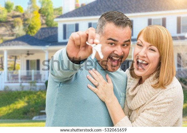 Happy Mixed Race Couple in Front of New Home with House Keys.