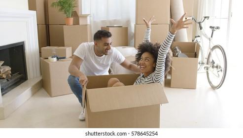 Happy mixed race couple having fun break with unpacking