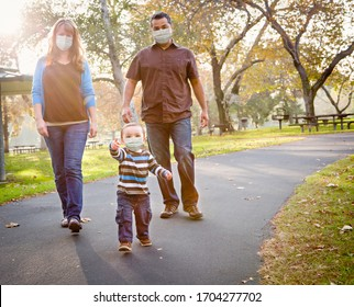 Happy Mixed Race Ethnic Family Walking In The Park Wearing Medical Face Mask. - Shutterstock ID 1704277702