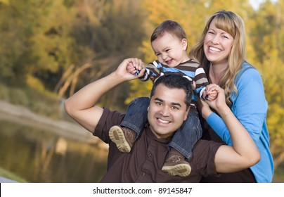 Happy Mixed Race Ethnic Family Posing for A Portrait in the Park.