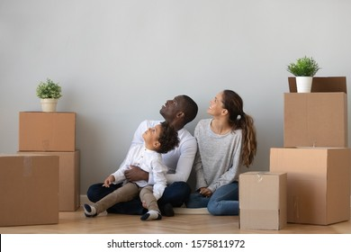 Happy mixed race family of african american father, mother and cute little curious son sitting on floor between big cardboard boxes, inspecting new apartment, discussing first house renovation ideas.