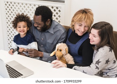 Happy mixed race family, african father, caucasian mother, using computer to make video call in quarantine, modern family using watch multimedia content and surf the internet