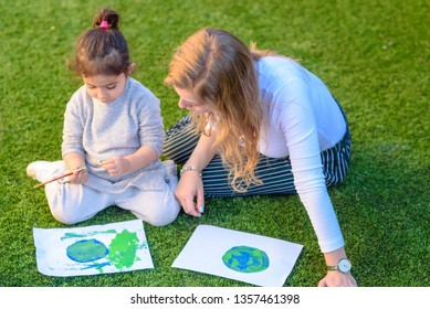 Happy mixed race family. Beautiful little girl and mom drawing a picture of earth globe. Children painting with brush and color a picture of earth.Earth day, plastic free and zero waste concept.