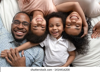 Happy mixed race family of four lying on bed cuddling, smiling african american dad mom and little kids bonding looking at camera, loving black parents children unity connection, portrait, top view