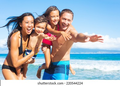 Happy Mixed Race Family of Four Playing and Having Fun on the Beach. Tropical Beach Family Vacation.