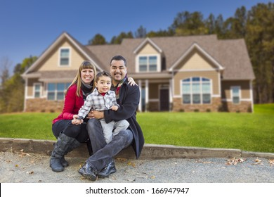 Happy Mixed Race Family in Front of Their Beautiful New Home.