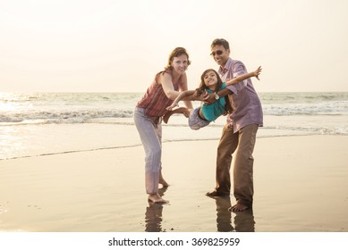 Happy mixed race family having fun on the beach at sunset. Parents playing with child.