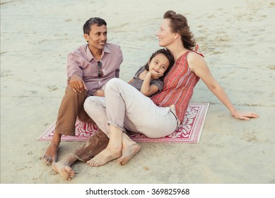 Happy mixed race family having fun on the beach at sunset