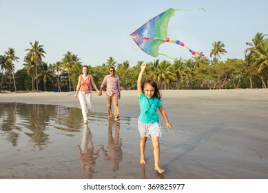 Happy mixed race family having fun on the beach at sunset. Parents playing with child. Child running on beach with kite in the hands