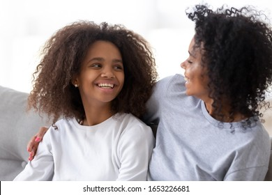 Happy mixed race family mom sister hugging teen daughter laughing talking sitting on sofa, cheerful teenage girl looking at african mother cuddling embracing having fun feeling love and joy at home