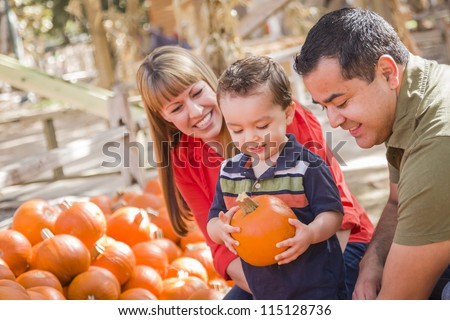 Happy Mixed Race Family Picking Pumpkins at the Pumpkin Patch.