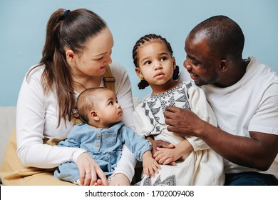 Happy mixed race family posing for a family photo in a studio. Black father, white moher and their two little daughters over blue background. Looking at elder girl.