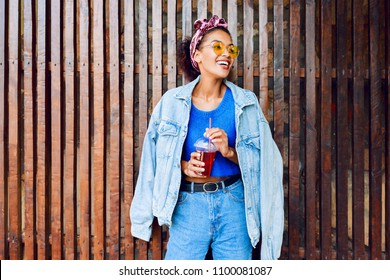 Happy mixed race female with stylish Afro hairs posing outdoor , holding cherry lemonade , wearing jeans jacket and blue wool sweater.  Wood background .