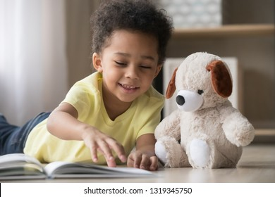 Happy mixed race little boy enjoying playing alone reading book to fluffy toy lying on warm floor, cute smiling african american kid having fun at home, creative child activity, underfloor heating
