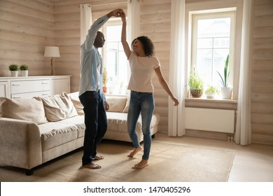 Happy mixed race married couple having fun together in modern cozy wooden living room, dancing, twisting on whitish carpet near comfortable couch. Smiling family spouse enjoying leisure weekend time.