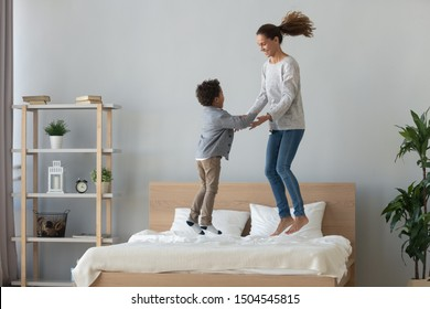Happy mixed race mother and little son dancing, jumping on bed, holding hands, laughing mom playing funny game with excited adorable preschool child in bedroom, family having fun on weekend