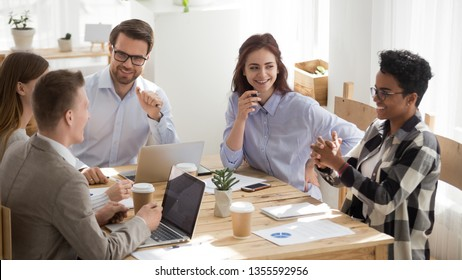 Happy mixed race office workers at business meeting having fun. Diverse men and women laughing sitting at desk, share ideas. Smiling black female speaker talking. Team work, team building concept