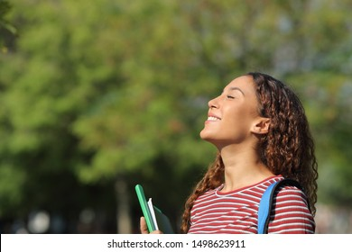 Happy mixed race student breathing deeply fresh air standing in a park or campus