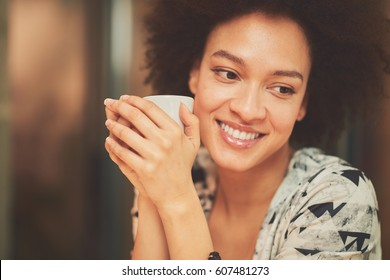 Happy mixed race woman having a coffee in coffee shop