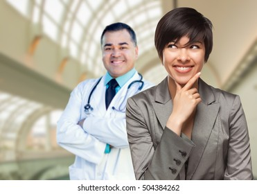 Happy Mixed Race Woman Looking To The Side As Hispanic Male Doctor Stands Behind Her Inside Hospital.