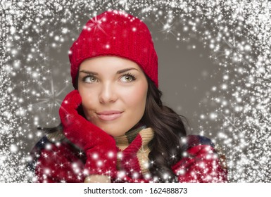 Happy Mixed Race Woman Wearing Winter Hat and Gloves Enjoys Watching the Snow Fall Looking to the Side on Gray Background.