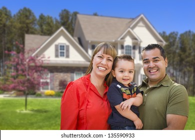 Happy Mixed Race Young Family in Front of Beautiful House.