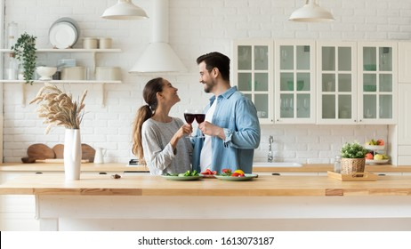 Happy mixed race young woman cheering glasses of red wine with smiling man, enjoying romantic family time in modern kitchen. Excited married couple spending free weekend time together at home.