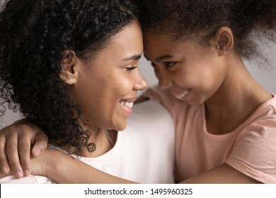 Happy mixed-race pre-teen daughter embraces loving mother close up faces family portrait, children is gift most important thing in life, warm relationships, strong connection, deep devotion concept