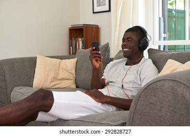 happy mobile cellphone african black man listening music sofa couch at home living room