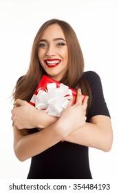 Happy model holding red present box in studio